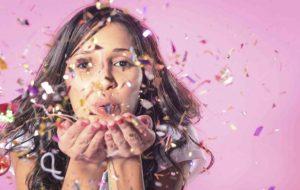 a women blowing a confetti