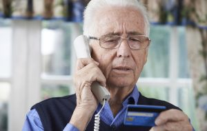 senior man giving credit card details on the phone
