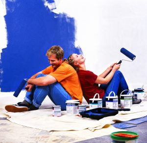 a couple sitting back to back with roller brushes of paint in hand